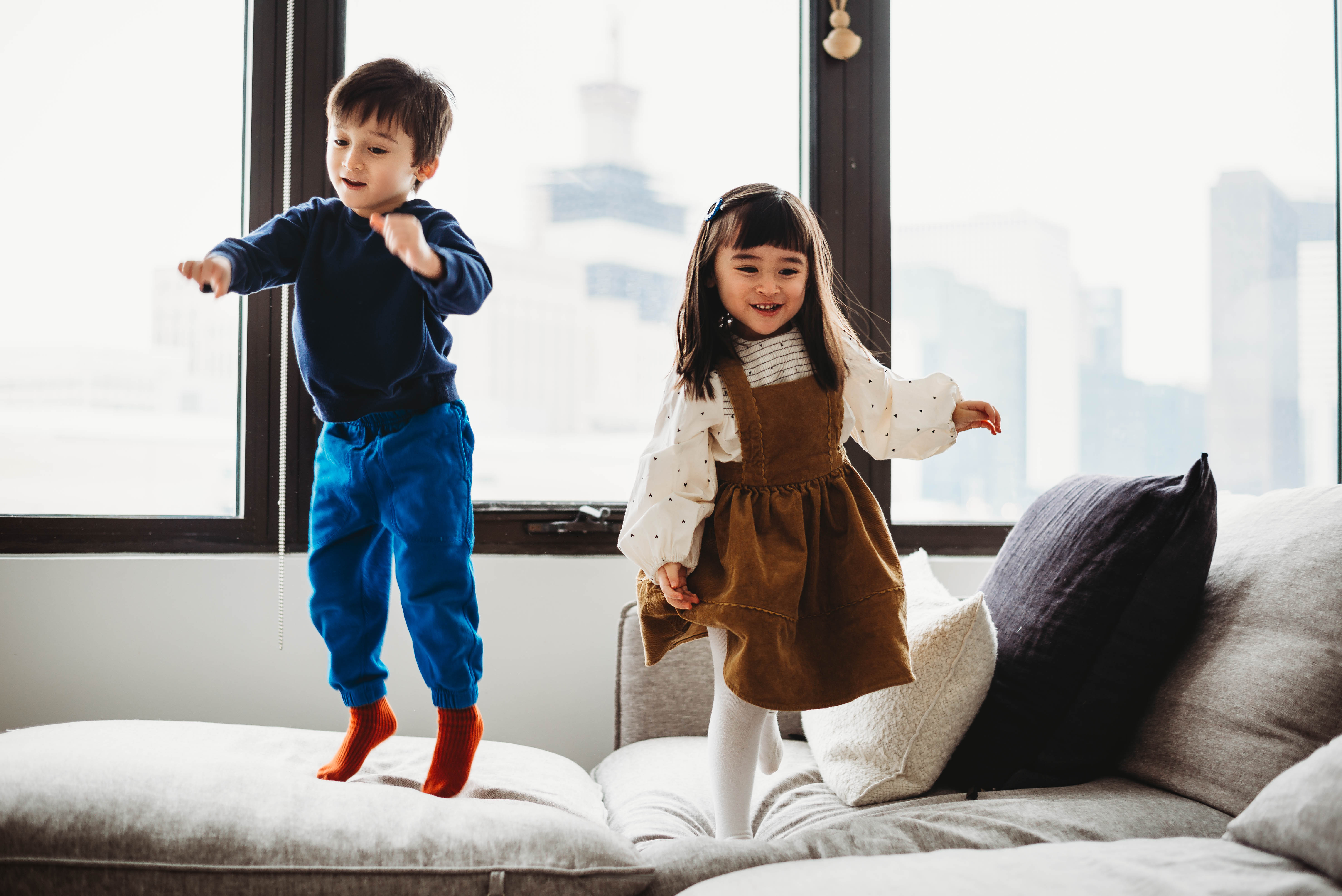 Three year old twin brother and sister jumping on the couch with the skyline of Chicago visible in the windows.