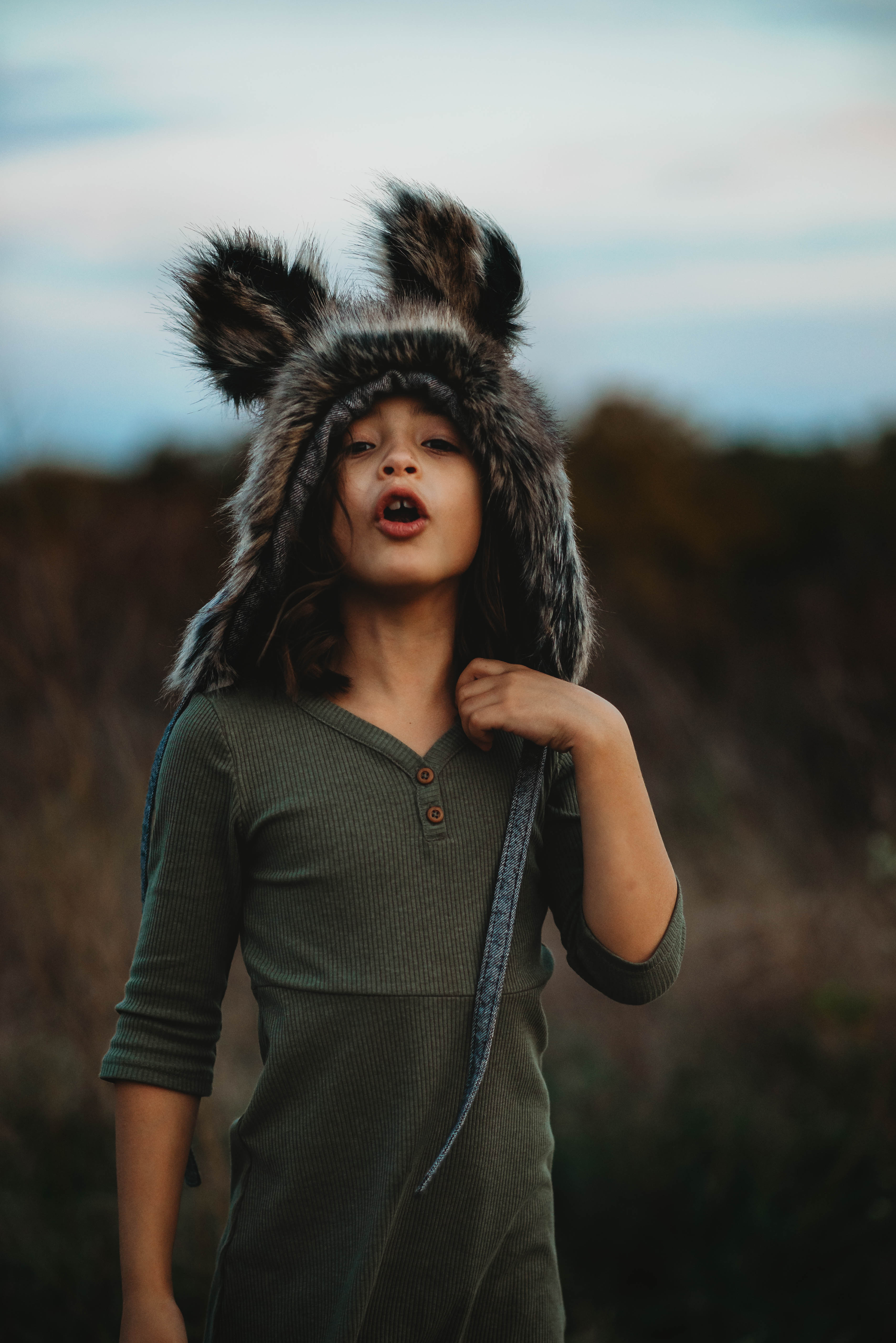 Young girl in green dress and Native Fable wolf bonnet pretending to howl at the setting sun.