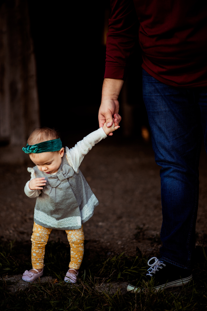 A one year old little girl with a green headband holding her daddy's hand as she takes steps.