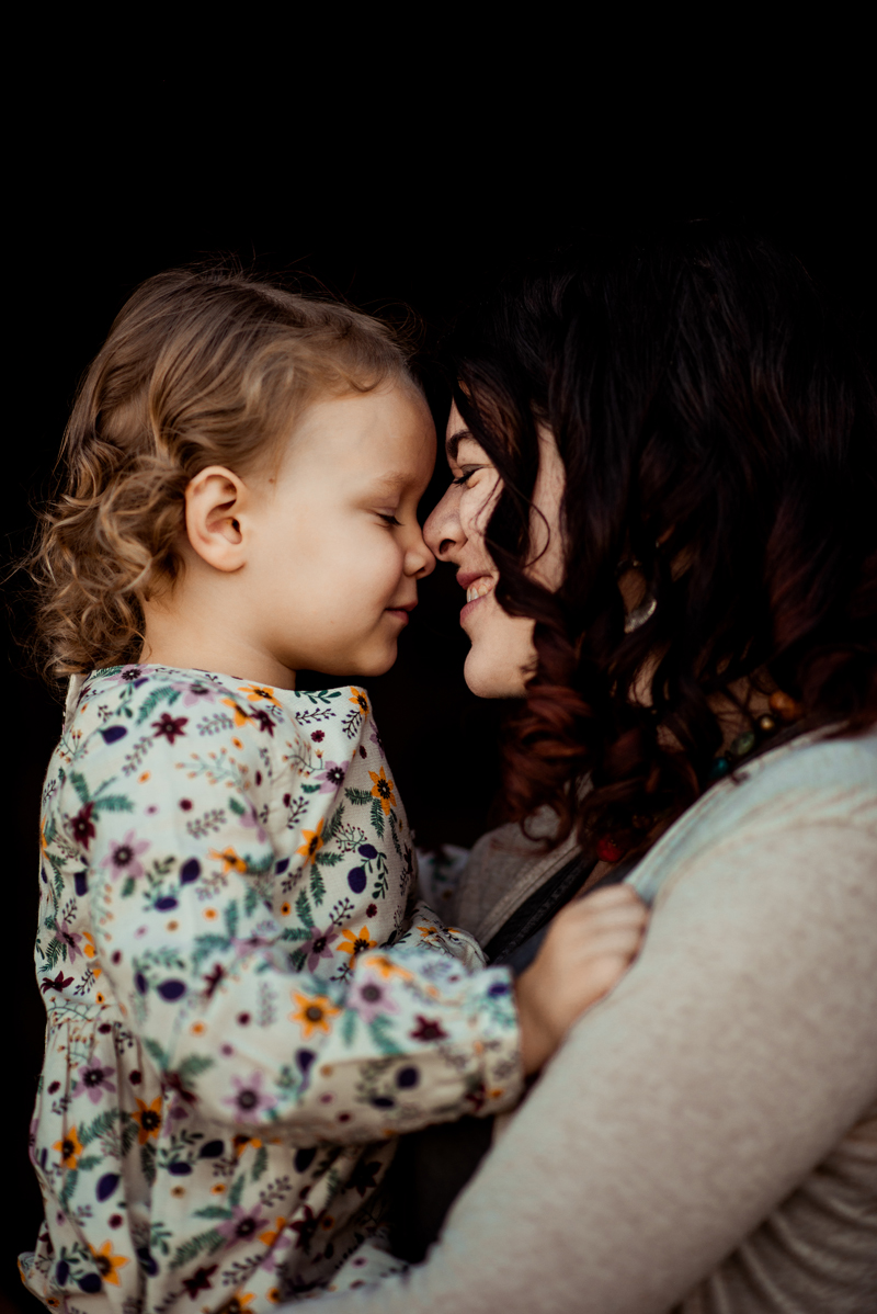 A sweet little girl with blonde curls giving noses kisses to her mommy.