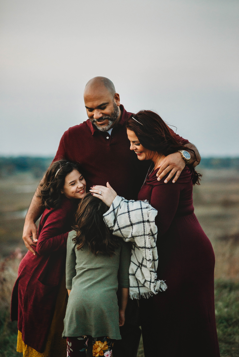 Family of four hugging at sunset at the top of a hill.